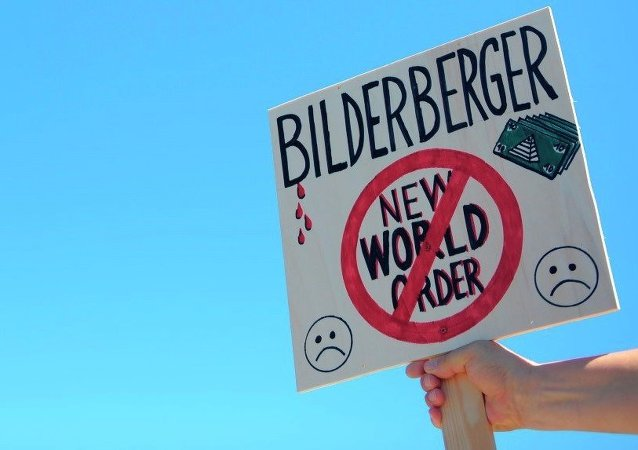 An activist protests near the meeting place for the conference of the Bilderberg Group