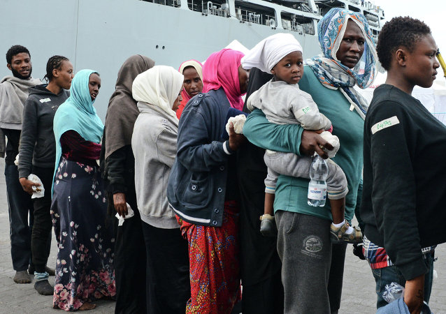 Migrants disembark from the Royal Navy ship HMS Bulwark upon their arrival in the port of Catania on the coast of Sicily on June 8, 2015