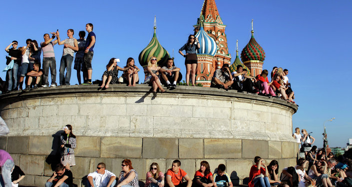 People sit at the Lobnoye Mesto, also known as the Place of Skulls, at Red Square enjoying a sunny day in downtown Moscow, Russia, Sunday, June 12, 2011