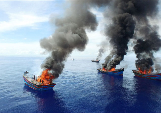 Columns of black smoke rise from four Vietnamese boats in the waters off Palau.