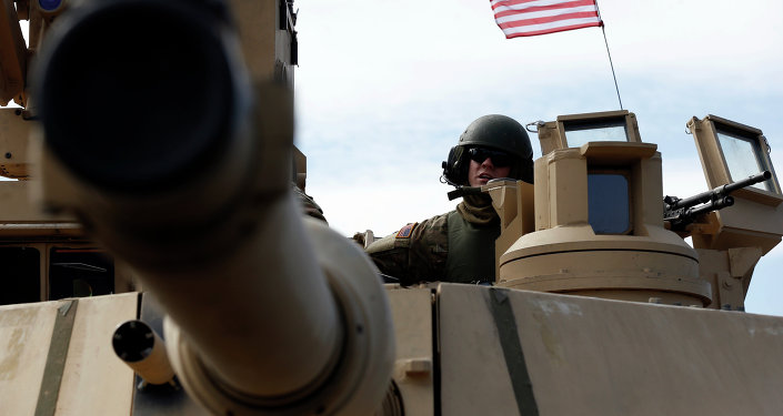 A U.S. soldier from the 2nd Battalion, 1st Brigade Combat Team, 3rd Infantry Division ride on an M1A2 Abrams battle tank during a military exercise at the Gaiziunu Training Range in Pabrade some 60km.(38 miles) north of the capital Vilnius, Lithuania