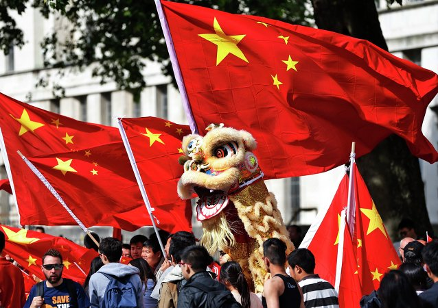 Chinese students hold a puppet depicting a dragon and  wave their national flags