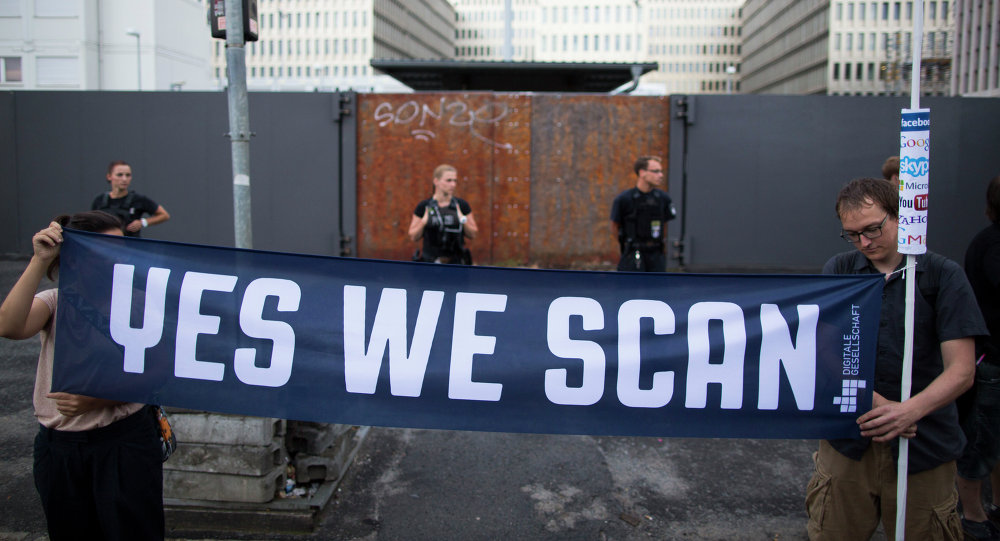 Demonstrators hold a banner during a protest against the supposed surveillance by the US National Security Agency, NSA, and the German intelligence agency, BND, during a rally in front of the construction site of the new headquarters of German intelligence agency in Berlin, Germany