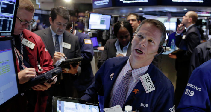 Robert Charmak, right, works with fellow traders on the floor of the New York Stock Exchange, Wednesday, June 10, 2015