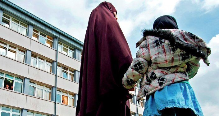 A woman and her child stand in front of the reception center for refugees in Schneeberg, eastern Germany.