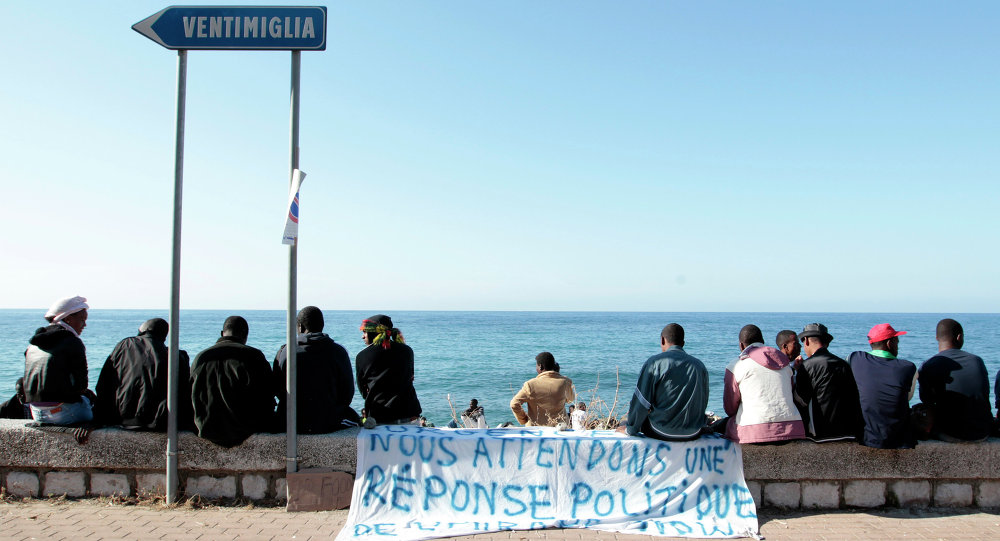Migrants sit near a banner reading We are waiting fo a political response on the shores of the Mediterranean sea in the Italian Franco-Italian border city of Ventimiglia on June 15, 2015, as they wait to cross into France