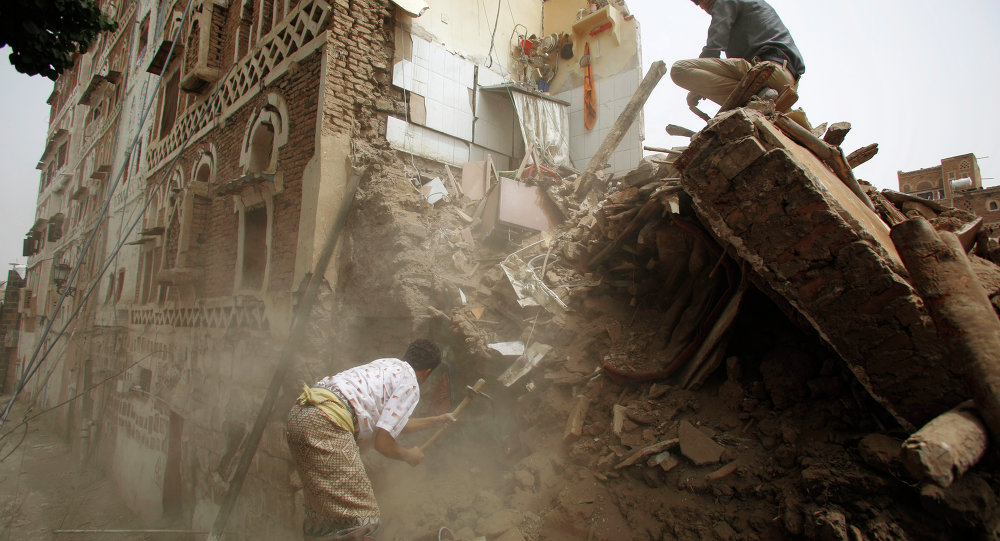 A man searches for survivors under the rubble of houses destroyed by Saudi airstrikes in the old city of Sanaa, Yemen, Friday, June 12, 2015