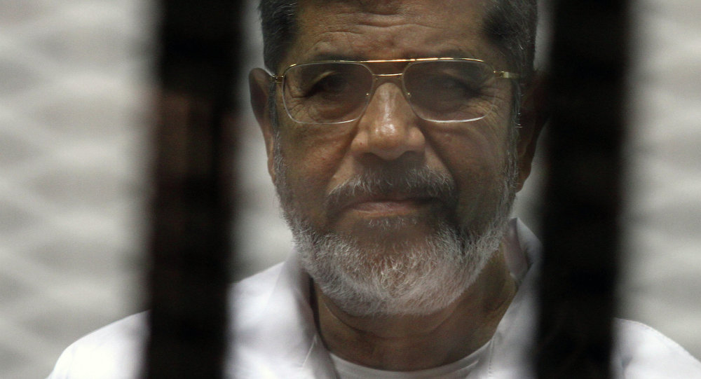 Egyptian ousted Islamist president Mohamed Morsi looks on from behind the defendants cage during is trial on May 8, 2014