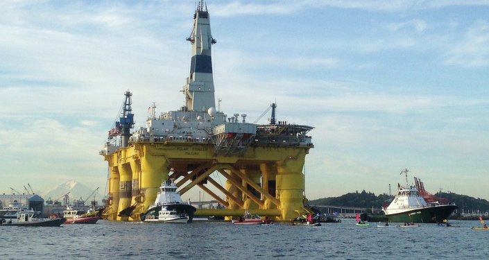"""This June 15, 2015 phto shows kayakers trying to block the departure of the Shell Oil """"Polar Pioneer"""" rig platform as it moved from Elliott Bay in Seattle, Washington"""