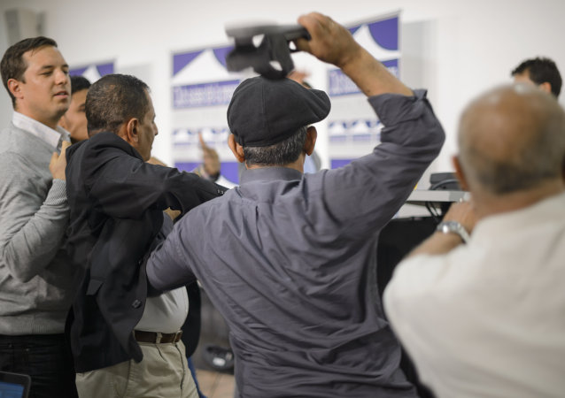 A representative of South Yemen throw a shoe at members of a rebel delegation during clashes at a press conference on Yemen peace talks in Geneva on June 18, 2015