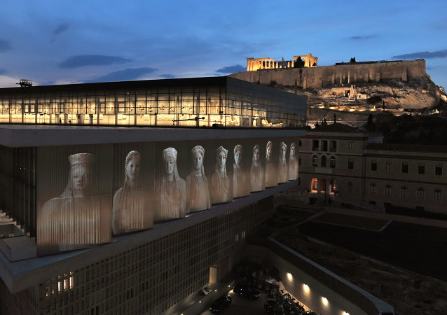 A projection depicting core-women statues is seen under the Parthenon hall on the new Acropolis museum building
