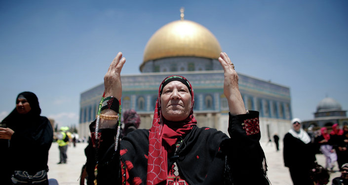 Palestinian Muslim worshipers pray outside the Dome of the Rock at the Al-Aqsa Mosque compound in Jerusalem during the first Friday prayer of the holy month of Ramadan, on June 19, 2015