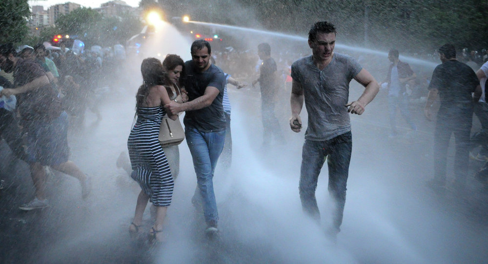 Armenian police use water cannons to disperse protesters demonstrating against an increase in electricity prices in the Armenian capital of Yerevan, Tuesday, June 23, 2015