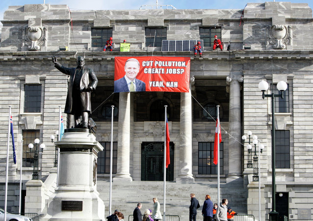Four Greenpeace environmental protesters perch themselves on a ledge above the main entrance of parliament buildings in Wellington, New Zealand, Thursday, June 25, 2015