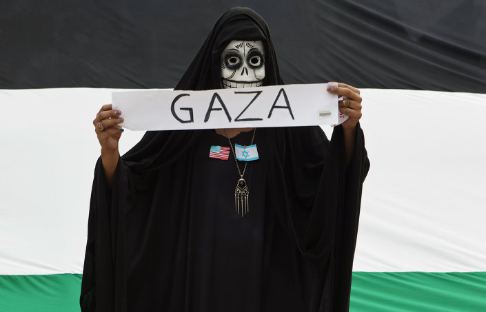 A protester wears a skull face mask during a protest against Israel's military action in the Gaza Strip, in Mexico City, Saturday, Aug. 9, 2014.
