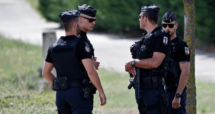 Police officers guard the road leading to a plant where an attack took place in Saint-Quentin-Fallavier, southeast of Lyon, France, Friday, June 26, 2015