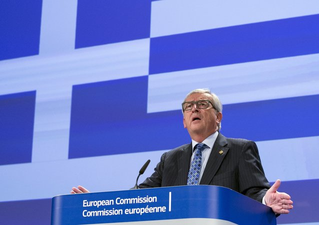 European Commission President Jean-Claude Juncker gives a statement while standing in front a giant Greek flag projected in the press room at the EU commission headquarters in Brussels, Belgium June 29, 2015