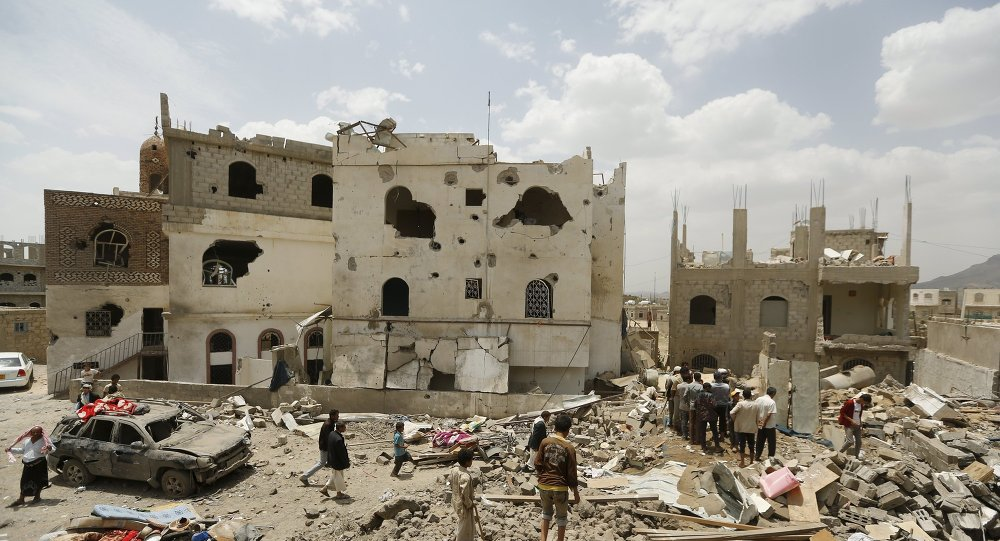 People walk on the rubble of houses destroyed by a Saudi-led air strike