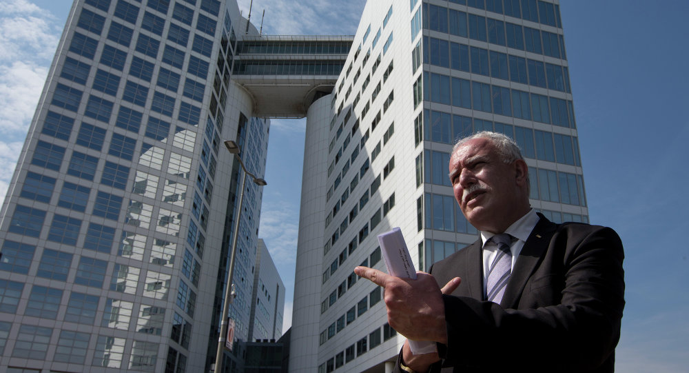 Palestinian Foreign Minister Riyad Al-Maliki waits to give an interview outside the International Criminal Court, rear, in The Hague, Netherlands, Thursday, June 25, 2015