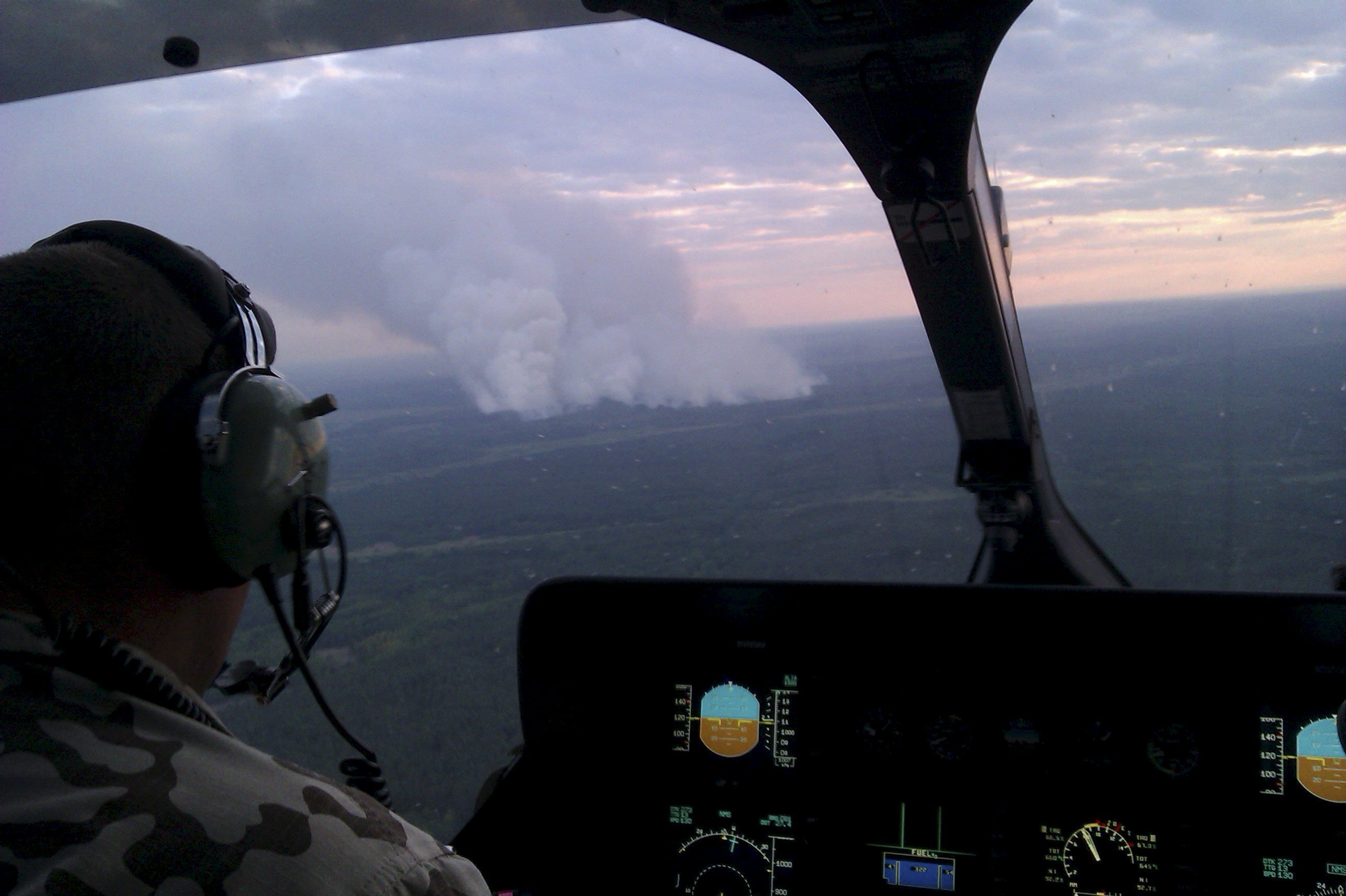 An aerial view from a helicopter shows smoke from forest fires some 40 km from Chernobyl nuclear power plant in Kiev region, northern Ukraine, June 29, 2015. Picture taken with a mobile phone on June 29, 2015