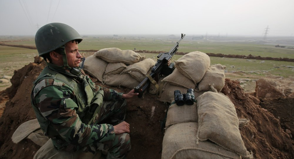 In this Tuesday, Jan. 27, 2015 photo, a Kurdish Peshmerga soldier stands guard, overlooking the road between Mosul and Tal afar at the frontline of Eski Mosul.