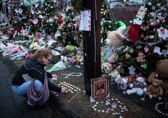 A woman lights candles at a makeshift memorial near the entrance to the grounds of Sandy Hook Elementary School on December 18, 2012 in Newtown, Connecticut