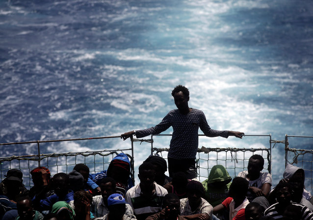 File Photo: Migrants sit on the deck of the Belgian Navy vessel Godetia after they were saved at sea during a search and rescue mission in the Mediterranean Sea off the Libyan coasts, Wednesday, June 24, 2015.