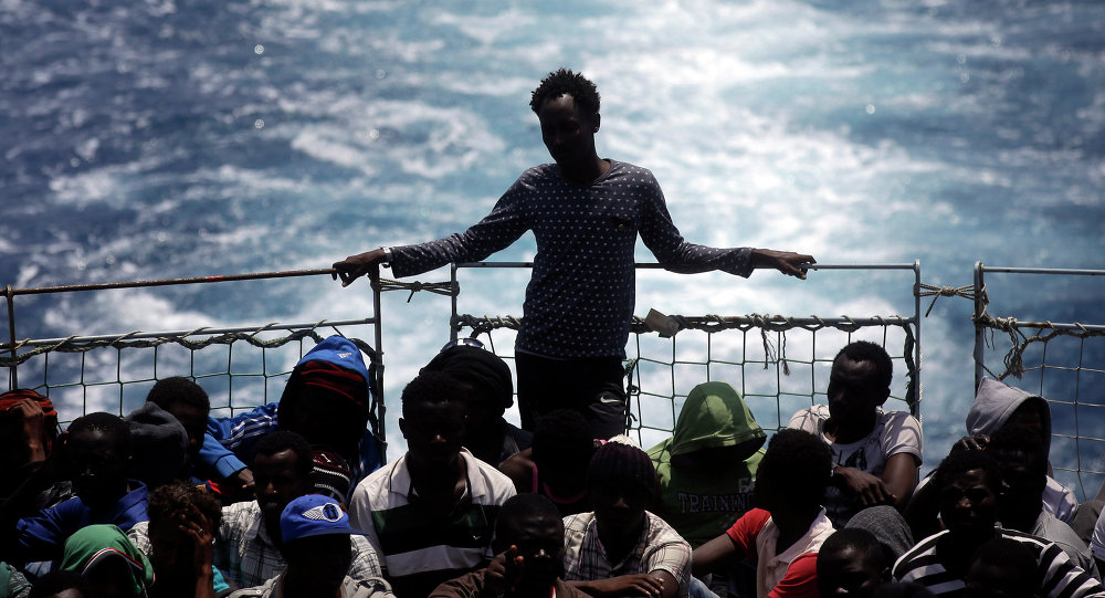 Migrants sit on the deck of the Belgian Navy vessel Godetia after they were saved at sea during a search and rescue mission in the Mediterranean Sea off the Libyan coasts, Wednesday, June 24, 2015.