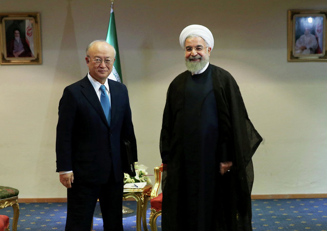 Iran's President Hassan Rouhani, right, welcomes the International Atomic Energy Agency's director-general, Yukiya Amano, as they pose for photos at the start of their meeting in Tehran, Iran, Thursday, July 2, 2015