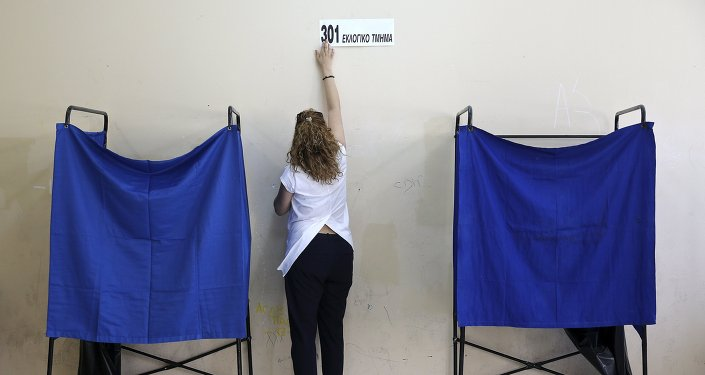 A referendum official puts up a sticker reading 301 polling station at an Athens high school that will be used as a polling station for Sunday's referendum in Greece, July 4, 2015