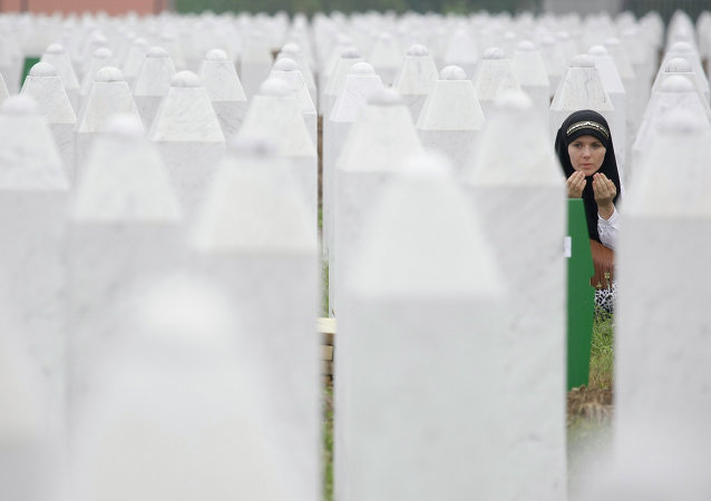 Bosnian woman Merima Nukic prays at the grave of her father during a funeral ceremony at the memorial center in Potocari, near Srebrenica, 160 kms east of Sarajevo, Bosnia