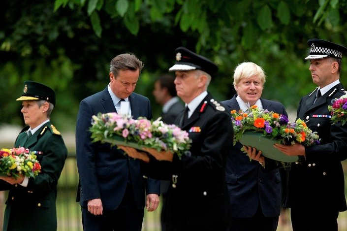 Britain's Prime Minister David Cameron, second from left, and London Mayor Boris Johnson, fourth from left, stand beside senior representatives from the ambulance, left, fire, third left, and police services as they wait to lay wreaths at the 7/7 memorial in Hyde Park in London, Tuesday, July 7, 2015.