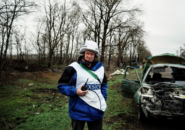 An International observer of the Organization for Security and Co-operation in Europe (OSCE) stands next to a destroyed car after shelling during an inspection tour near the village of Shirokino