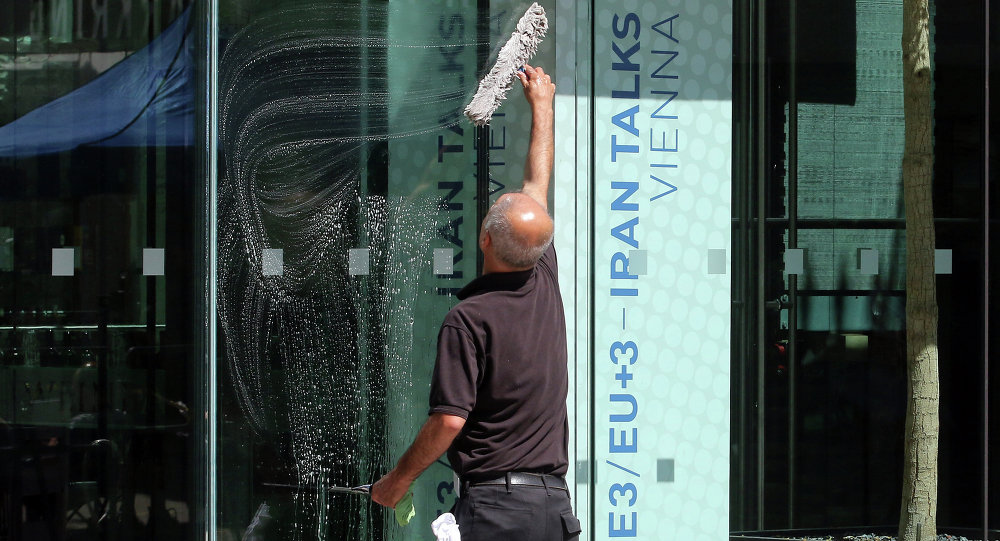 A man cleans the front door of Palais Coburg where closed-door nuclear talks with Iran take place in Vienna, Austria, Saturday, July 11, 2015