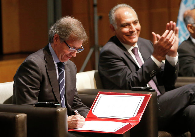 UN envoy to Libya, Bernardino Leon, left, signs the document on a new version of a UN-brokered peace deal as Morocco's Foreign Minister Salaheddine Mezouar applauds after Libyan political leaders agreed, at the Palais des Congres of Skhirate in Rabat, Morocco, Saturday, July 11, 2015