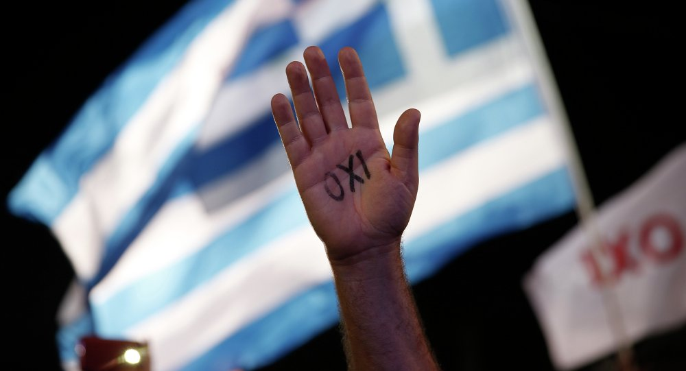 A demonstrator raises his hand with the word ''No'' written on it as a Greek flag waves behind during a rally organized by supporters of the No vote in Athens.