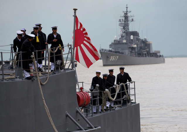 Japanese navy officers stand on the deck of a Japan Maritime Self-Defense Force vessel docked at Thilawa port, Myanmar, 30 September 2013