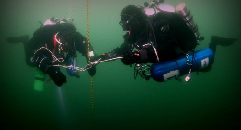 Members of the Russian Geographical Society's underwater scientific research crew conduct a descent in the Arctic.