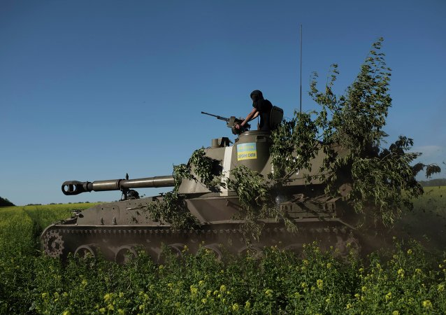 A Ukrainian serviceman rides atop an armored military vehicle to take their positions near Donetsk, eastern Ukraine, Sunday, June 7, 2015