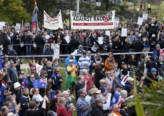 Opposing protest groups, from the Reclaim Australia anti-islam group (foreground) and those calling for an end to racism (background) are separated by a police line in Brisbane, July 19, 2015