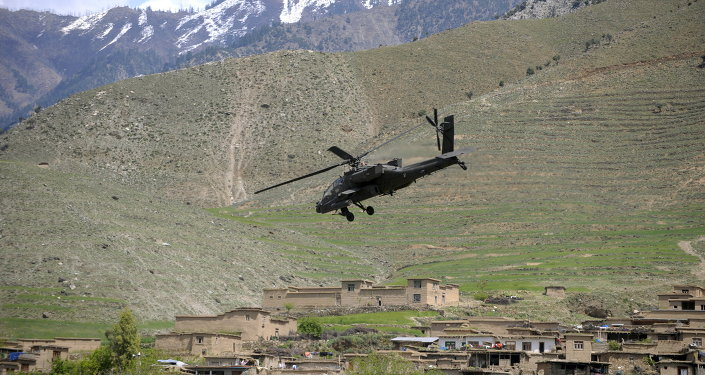 A US Army AH-64 Apache helicopter flies over a village in Naray, in Afghanistan's eastern Kunar province on April 16, 2009