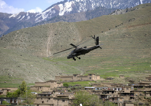 A US Army AH-64 Apache helicopter flies over a village in Naray, in Afghanistan's eastern Kunar province.file photo