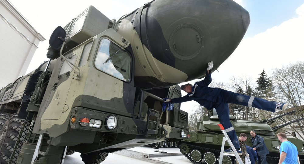 An employee cleans a Topol-M intercontinental ballistic missile launcher at an open-air military exhibition in Moscow on April 29, 2015