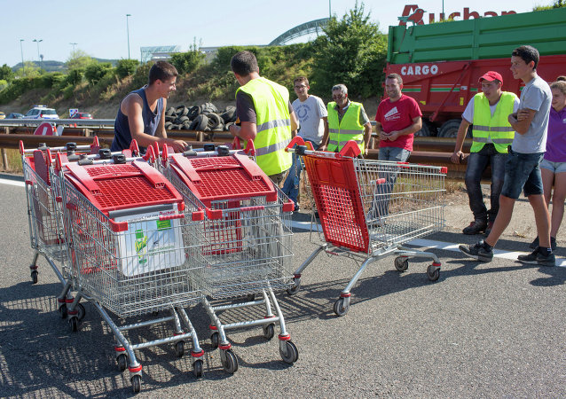 Farmers use tires and shopping carts to block the highway leading Paris to Lyon in Limonest near Lyon, central France, Thursday, July 23, 2015