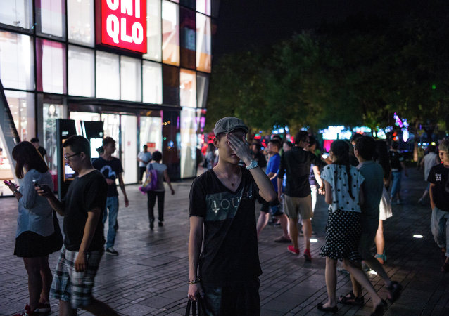 In this picture taken on July 15, 2015, people gather in front of a Uniqlo clothes store in Beijing.