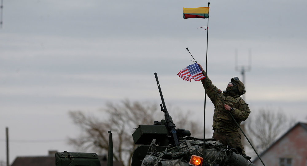 A member of US Army's 2nd Cavalry Regiment raises the US flag on a Stryker vehicle during the ''Dragoon Ride'' military exercise, in Salociai some 178 kms (110 miles) north of the capital Vilnius, Lithuania, Monday, March 23, 2015