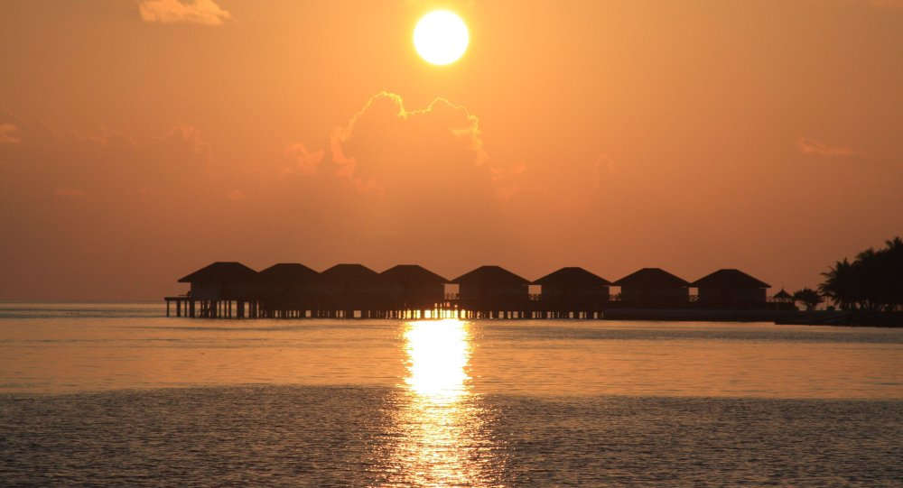 The sun sets over vacation cottages in the Maldives.