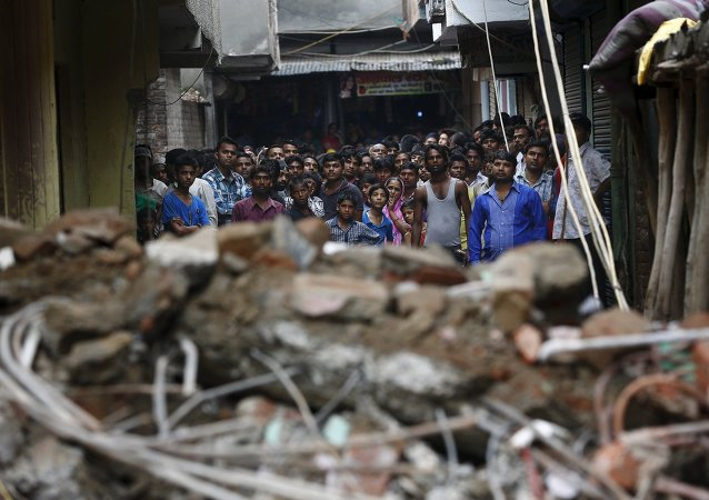 Onlookers stand at the site of a collapsed building