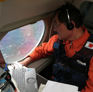Communications specialist Hidetaka Sato on a Japan Coast Guard Gulfstream aircraft, looks out of a window searching for the missing Malaysia Airlines Flight MH370 in Southern Indian Ocean, near Australia, Tuesday, April 1, 2014.