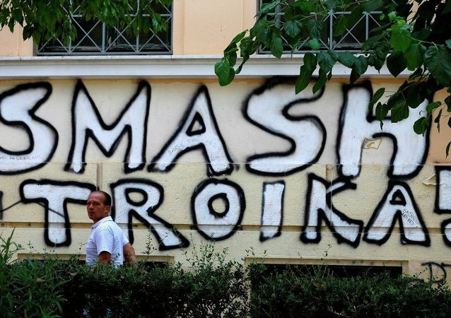 A pedestrian passes graffiti referring to the officials from the European Union, European Central Bank and International Monetary Fund, together known as the troika, in Athens, Wednesday, July 29, 2015.